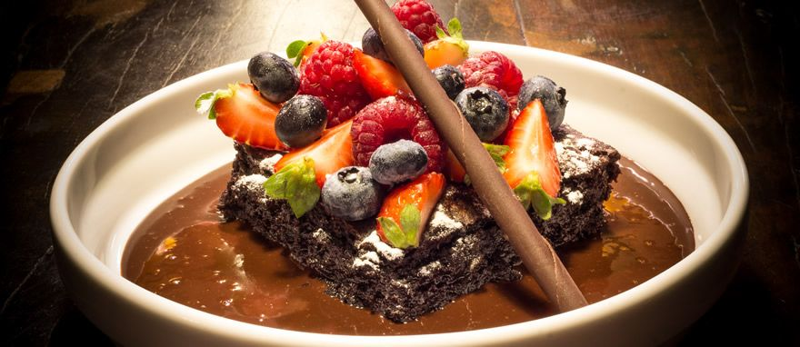 Brownie de chocolate, frutas vermelhas frescas e calda de chocolate.